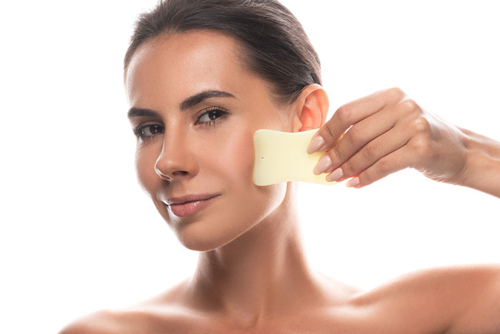 A woman uses gentle scraping with a smooth jade tool for Gua Sha treatment on her face.