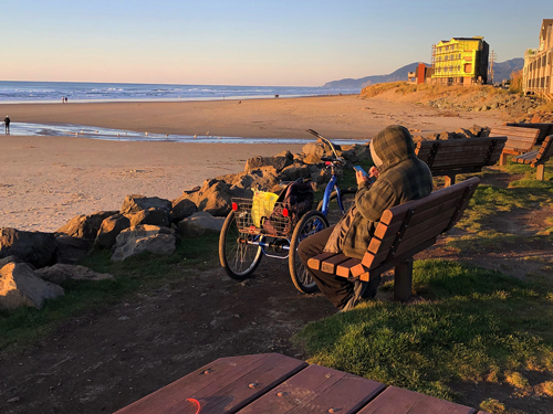 Some people come alone to watch the sunset on Thanksgiving Day on Rockaway Beach.