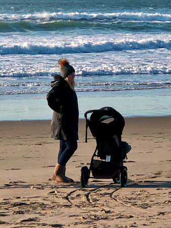A young mother and her baby visit the beach. Thanksgiving Day on Rockaway Beach OR.